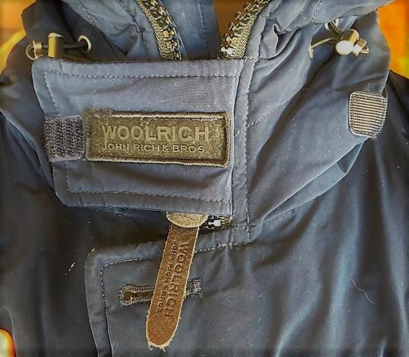 ブログ「モノオス」WOOLRICH(ウールリッチ)アークティックパーカのジッパーと、首もとにあるジッパー止めのタグを映した写真(ジッパー止めで止めている)
