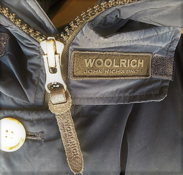 ブログ「モノオス」WOOLRICH(ウールリッチ)アークティックパーカのジッパーと、首もとにあるジッパー止めのタグを映した写真(ジッパー止めで止めていない)