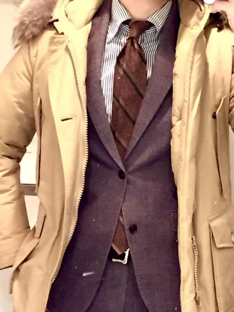 ブラウン色のウールリッチをスーツの上から着ている画像