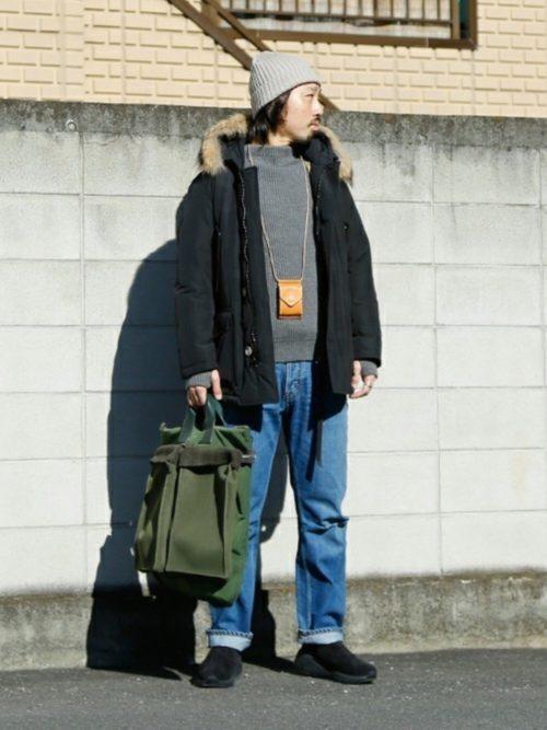 ねずみ色のセーターと薄めの色のジーンズの上にウールリッチを着ている画像