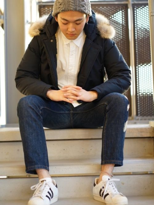 白シャツと濃いめの色のジーンズの上にウールリッチを着ている画像