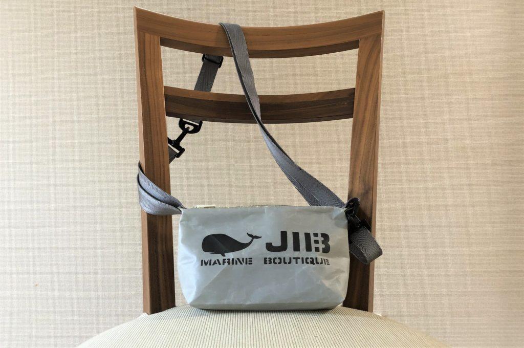 ブログ「モノオス」JIB(ジブ)のグレーのミニポーチにストラップを付けてショルダーバッグにしたものを椅子に置いて正面から撮った写真
