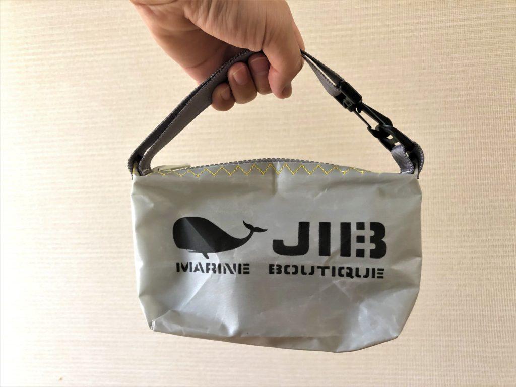ブログ「モノオス」JIB(ジブ)のグレーのミニポーチを手で持っているところを正面から撮った写真
