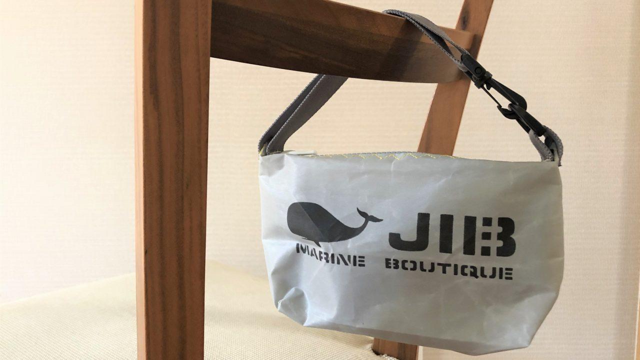 ブログ「モノオス」JIB(ジブ)のグレーのミニポーチのハンドルを椅子にかけて正面から撮った写真