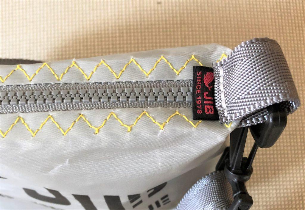 ブログ「モノオス」JIB(ジブ)のグレーのミニポーチのファスナー端に付いているJIBのタグを撮った写真