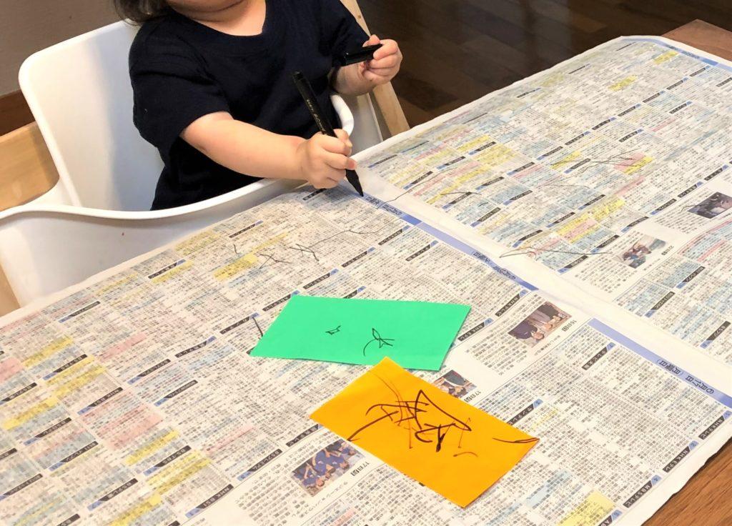 ブログ「モノオス」ストッケのトリップトラップ(オーク素材オークナチュラル色)に座ってダイニングで絵を描く赤ちゃんを撮った画像