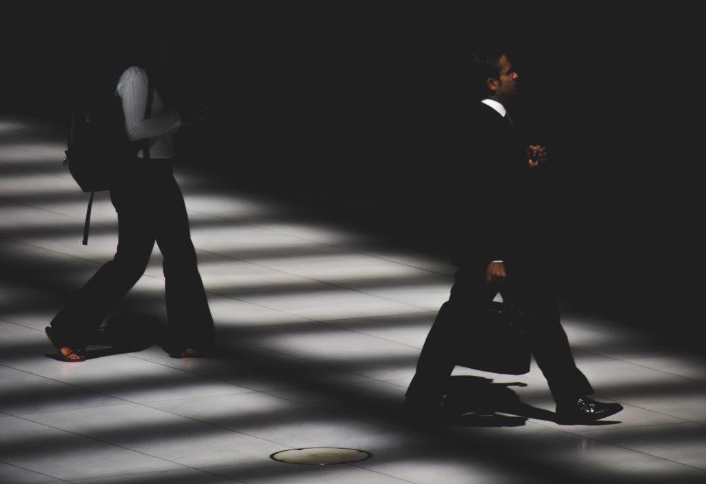 ブログ「モノオス」快適に働く手段として、リュックで通勤することをおすすめする。ビジネスバッグで歩いているサラリーマンとリュックで歩く女性の画像