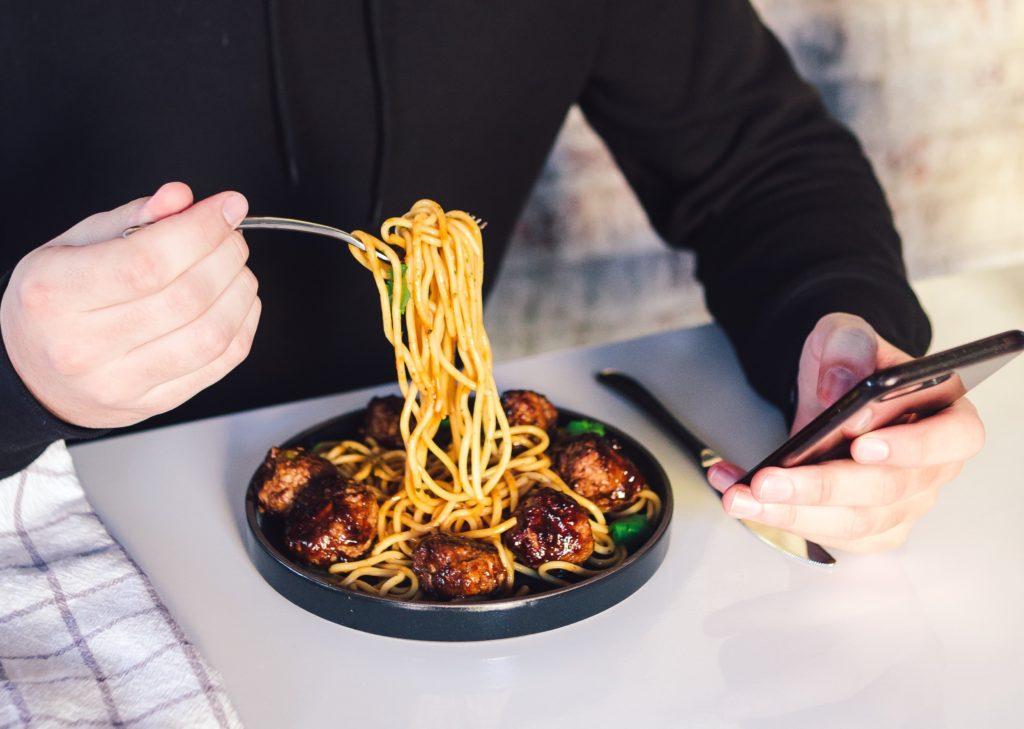 ブログ「モノオス」快適に働く手段として、お弁当を食べることをおすすめする。スマホをいじりながらパスタを食べる画像