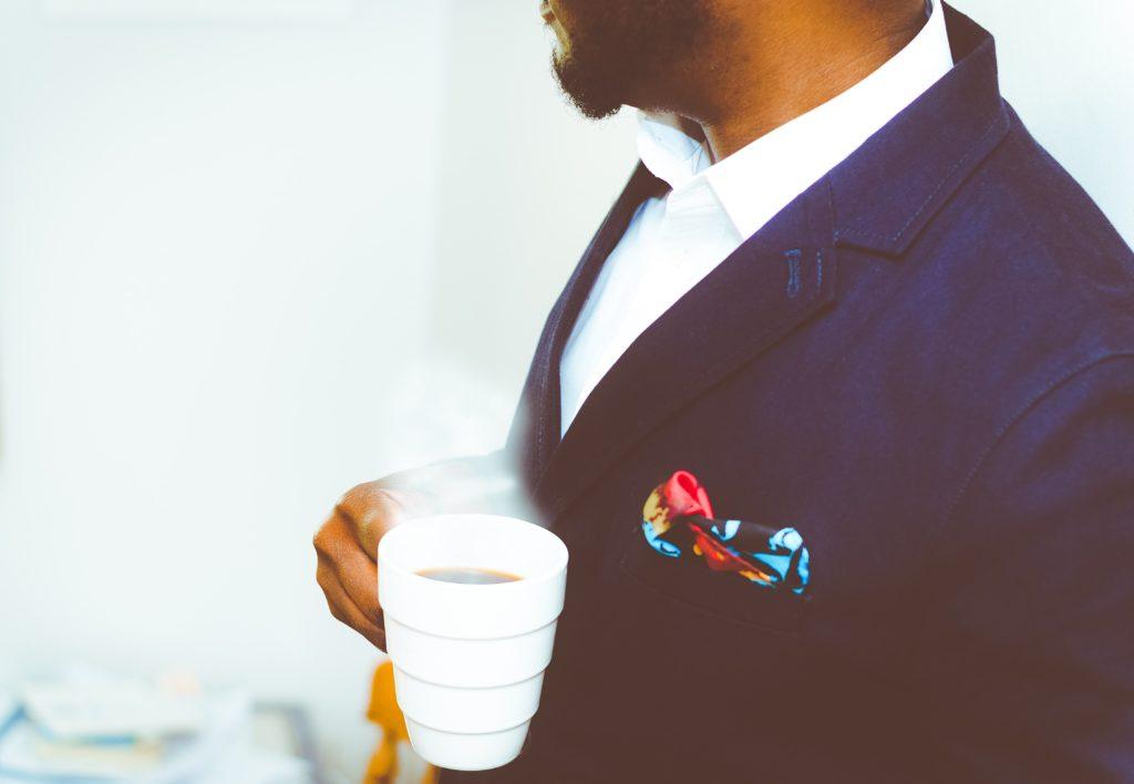 ブログ「モノオス」快適に働く手段として、お気に入りのドリンクを持ってくることをおすすめする。コーヒーを飲むサラリーマンの画像を撮った画像