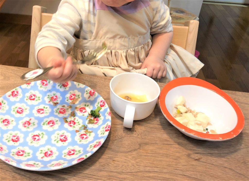 ブログ「モノオス」マールマールのエプロン・ブーケ1を着て食卓でご飯を食べているところを正面から撮った画像