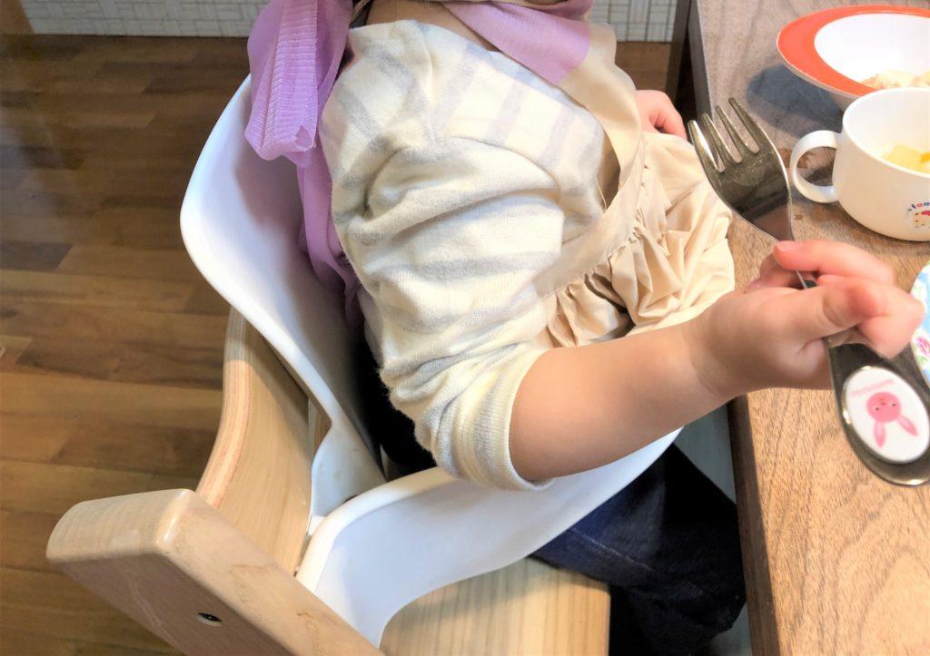 ブログ「モノオス」マールマールのエプロン・ブーケ1を着てストッケのイスに座って食卓でご飯を食べているところを横から撮った画像