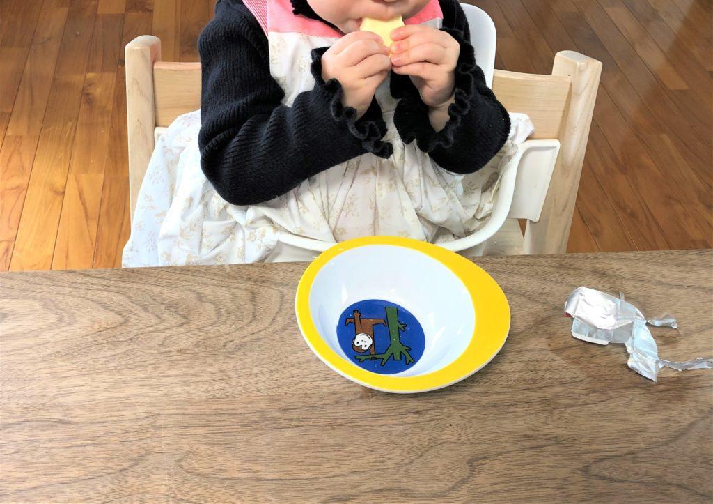 ブログ「モノオス」マールマールのエプロン・ブーケ5を着て食卓でチーズを食べているところを正面から撮った画像