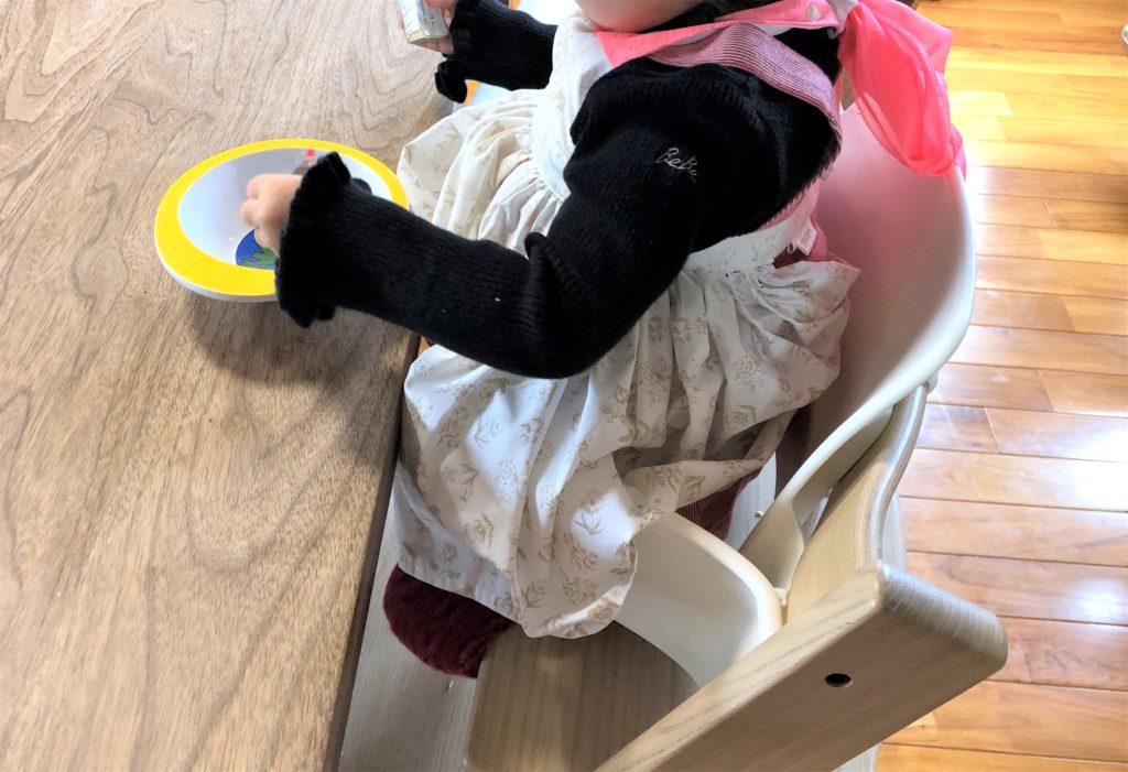 ブログ「モノオス」マールマールのエプロン・ブーケ5を着て食卓でチーズを食べているところを横から撮った画像