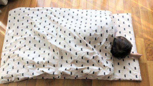 ブログ「モノオス」ディモアのベアマスクおひるねふとんセット(筒形バッグ)で、敷き・掛け両方がクロクマのふとんに子供が寝ている画像