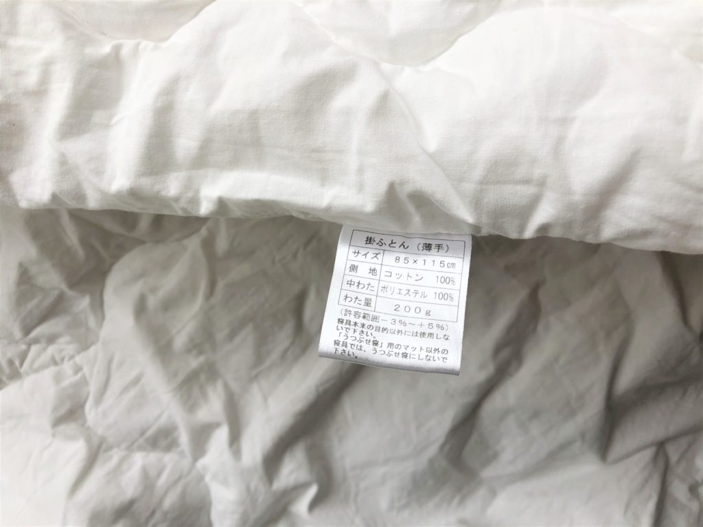 ブログ「モノオス」ディモアのベアマスクおひるねふとんセット(筒形バッグ)のかけぶとんのタグを撮った画像